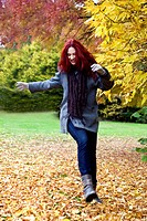 A young woman kicking leaves in autumn time