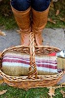 Close_up of a young woman's feet and wicker basket