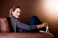 A mid adult woman relaxing in an armchair (thumbnail)