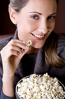 A mid adult woman eating popcorn