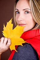 A mid adult woman holding an autumn leaf