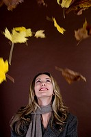 A mid adult woman smiling at falling autumn leaves (thumbnail)