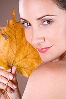 Portrait of a mid adult woman holding a dried leaf (thumbnail)