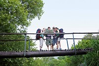 Four teenagers 16_17 years backpacking in forest reading map on bridge