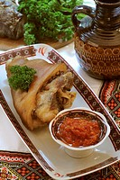 Traditional Russian and Ukrainian cuisine: grilled pork nuckle with spicy tomato sauce