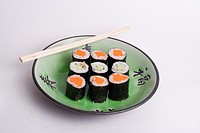 Small plate of carrot, cucumber, white rick, sesame seeds, vegetarian rolls won a decorative Japanese green plate