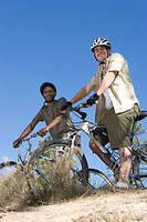 Two men stand with mountainbikes on hilltop