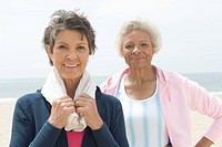 Two senior women stand on coastal promenade