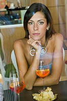 Young woman with a glass of orange wine