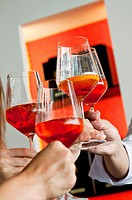 Closeup of hands holding wine glasses and toasting