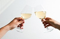 Closeup male and female hands holding wine glasses and toasting