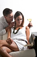 Young woman reading book on couch and young man with wine glass whispering in her ear