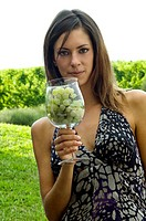 Young woman in vineyard with a wineglass of white grapes