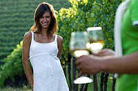 Young woman in vineyard, man bringing glasses of white wine