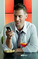 Young man sitting with a glass of orange wine and mobile phone