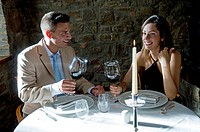Couple sitting at restaurant table toasting with red wine (thumbnail)