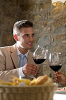 Young man at restaurant table toasting with wine held by woman's hand