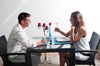 Couple sitting at table drinking white wine