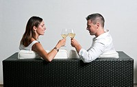 View of couple from the back sitting on couch toasting with white wine