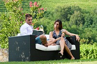 Young couple sitting on couch in vineyard with white wine, man reading book