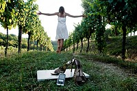 Young woman in vineyard with high heel shoes, mobile, and laptop in foreground