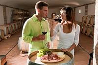 Couple in a wine cellar tasting red wine and antipasti (thumbnail)