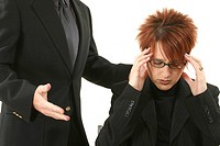 Businesswoman suffering from a headache with a businessman standing beside her