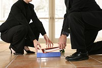 Low section view of a businessman and a businesswoman picking up notebooks from the floor
