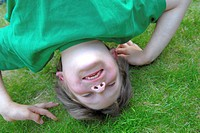 Close_up of a boy doing a headstand on grass