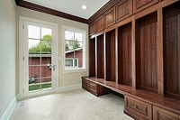 Mudroom in suburban home with side entry door