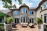 Back view of luxury home with rust colored patio