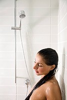 Head shot of woman in shower stall with low flow faucet
