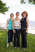 Three women in yoga wear at beach park, Vancouver, BC