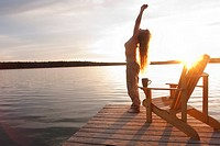Woman reaching upward on dock at sunset, Clear Lake, Manitoba, Canada