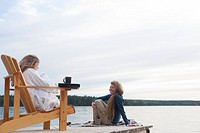 One woman seated in deck chair, second woman seated on dock with coffee, Clear Lake, Manitoba, Canada