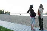Pregnant woman and friend on beach boardwalk, Clear Lake, Manitoba, Canada
