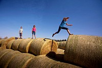 Twelve year old girl leaps between bales as 10 year old girl and 12 year old boy watch, Redvers, Saskatchewan, Canada