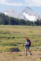 Woman hiking on a trail in a mountain meadow