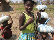 Young children carry bags of food on their heads after leaving an MSF feeding clinic  Feeding centres and other humanitarian aid were organised in Ang...
