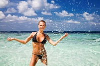tropical beach: perfect girl playing with water. Copy space