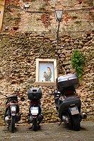 Three scooters parked in an Iatlian alley in front of a generic painting of Mary and the child Jesus. Perfect image of the old and modern Italy unifie...