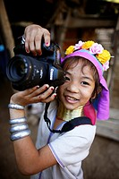 Longneck girl smiling as she plays with a camera  Approximately 300 Burmese refugees in Thailand are members of the indigenous group known as the Long...