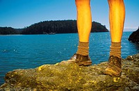 Legs of Hiker on Rocks by Ocean