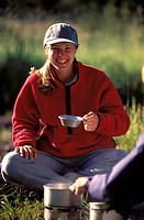 Woman Eating At Camp
