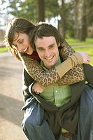 Young woman riding piggyback on a young man