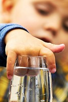 Child With Hand In A Water Glass