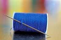 A Needle And Spool of Thread With Rainbow Colors