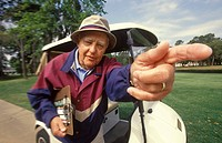 Elderly Man Walking Next To Golf Cart And Pointing Forward
