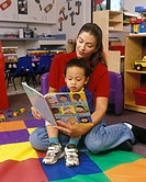 Teacher Reading Language Book To Asian American Boy
