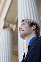 Businessman looks ahead and smiles as he stands in front of columns